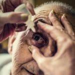 Senior man having eye drops put in