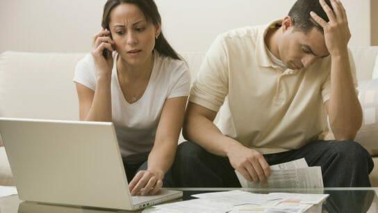 Hispanic couple having difficulty paying bills online.