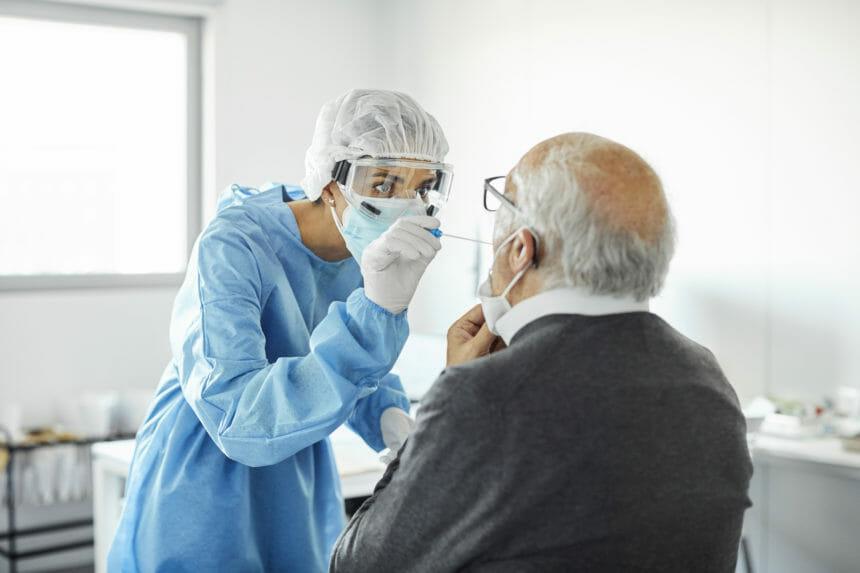 Doctor taking swab test sample of elderly patient, PCR.