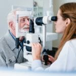 Female ophthalmic doctor diagnosing elderly patient`s sight using ophthalmic equipment